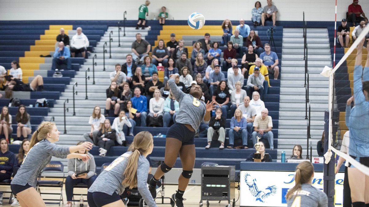 A girls volleyball player jumps in the air for a spike