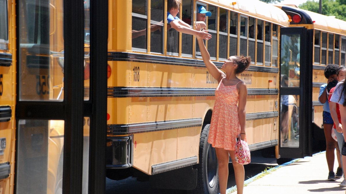 Girl stands next to bus and high fives with someone inside the bus