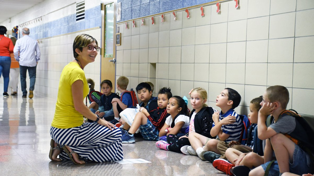 A teacher talks with her students lined up in the hall