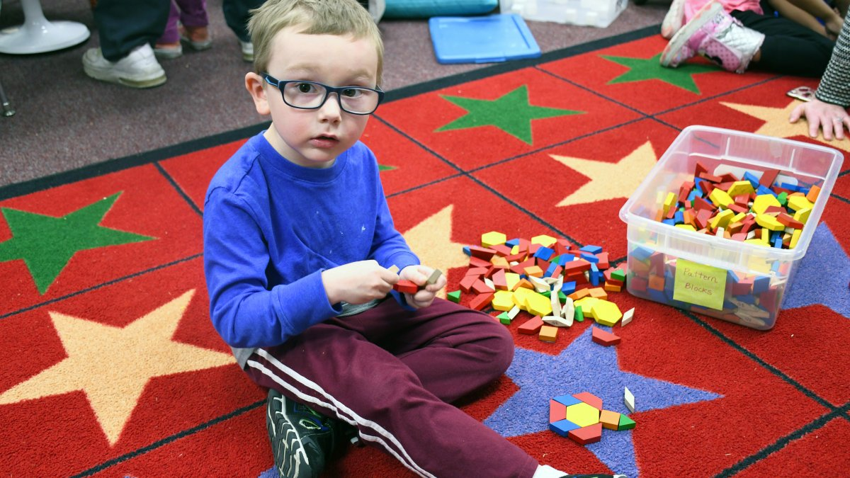 Student plays with shape pattern blocks