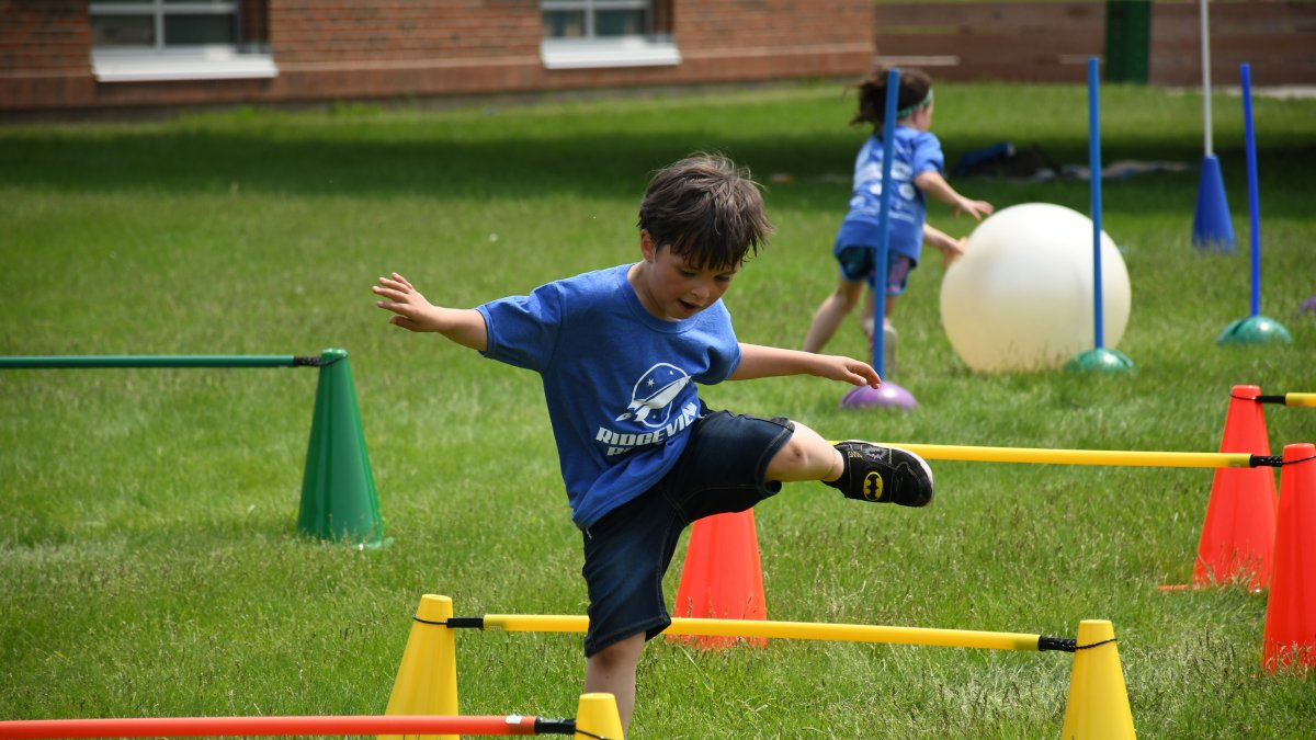 A student jumps over a hurdle during field day