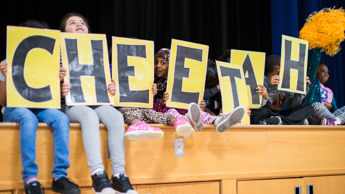 "Students hold up signs spelling ""CHEETAH"""