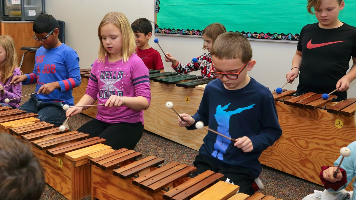Students play wooden xylophones