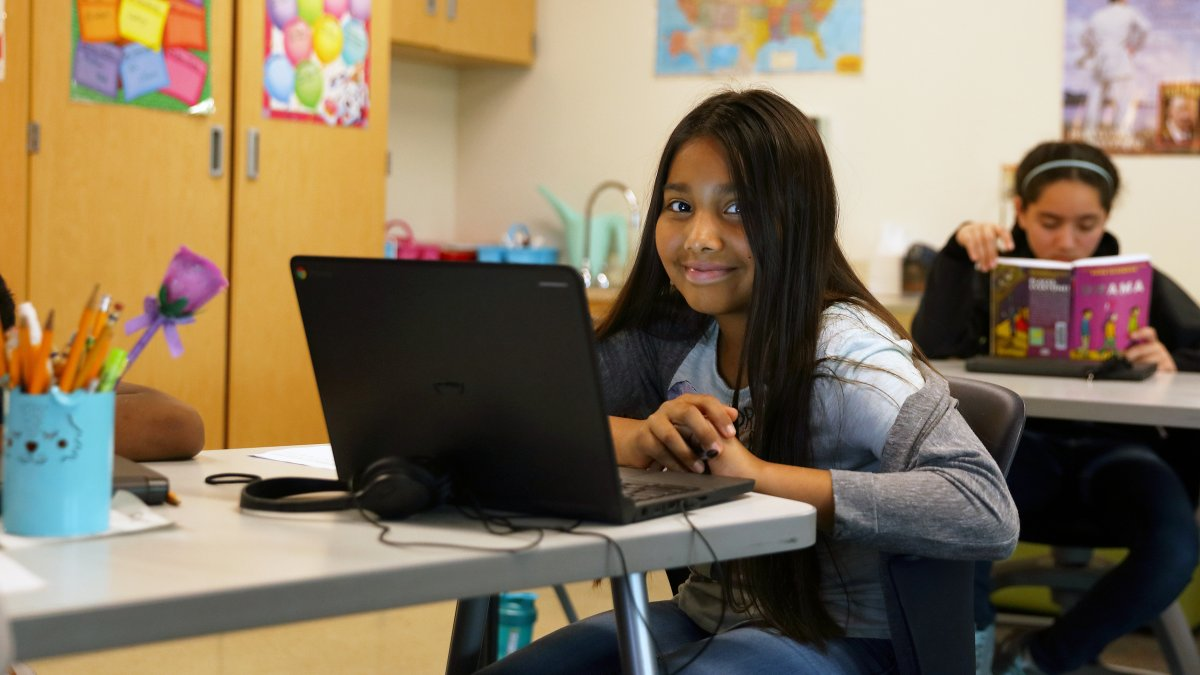 A student smiles while working on a laptop