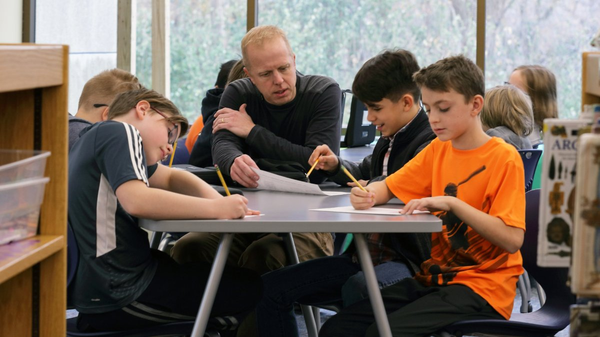 A teacher instructs a group of students at a table