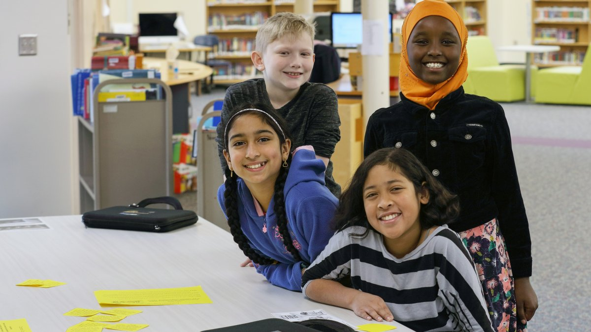 Four students smile in the media center