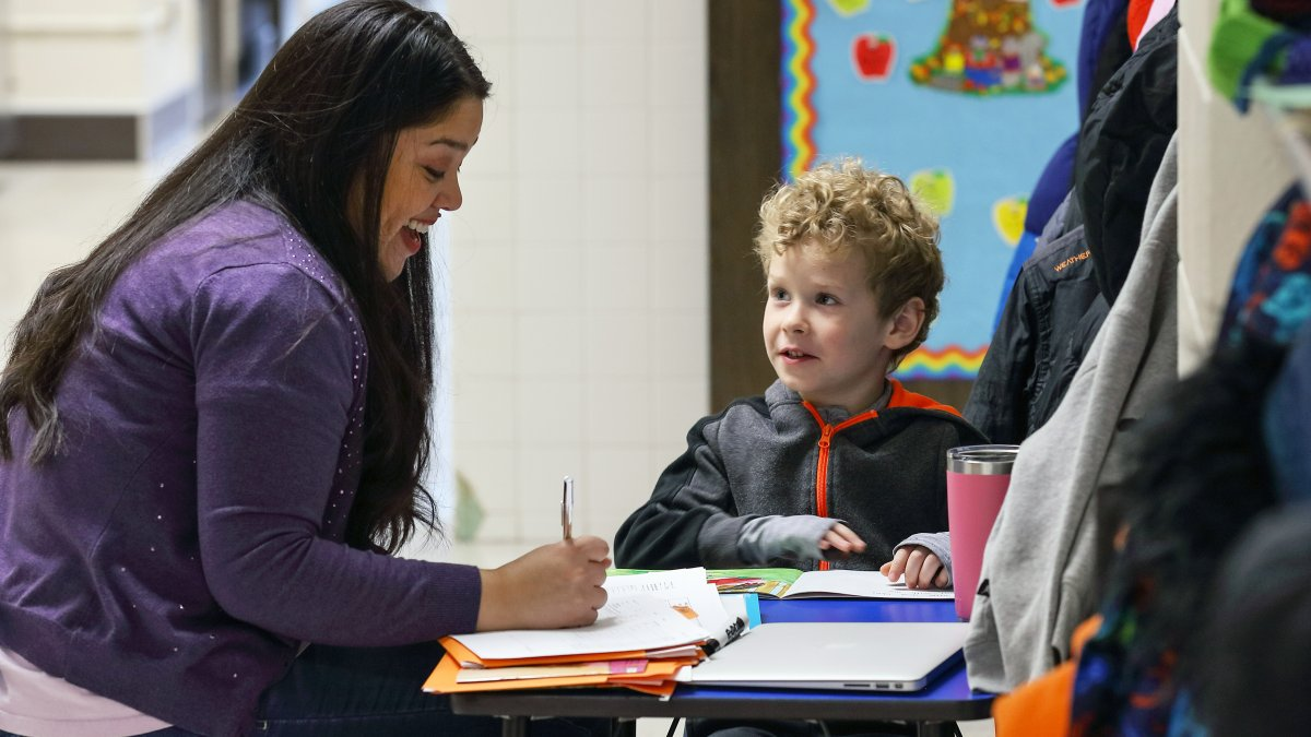 A staff member instructs a student one-on-one