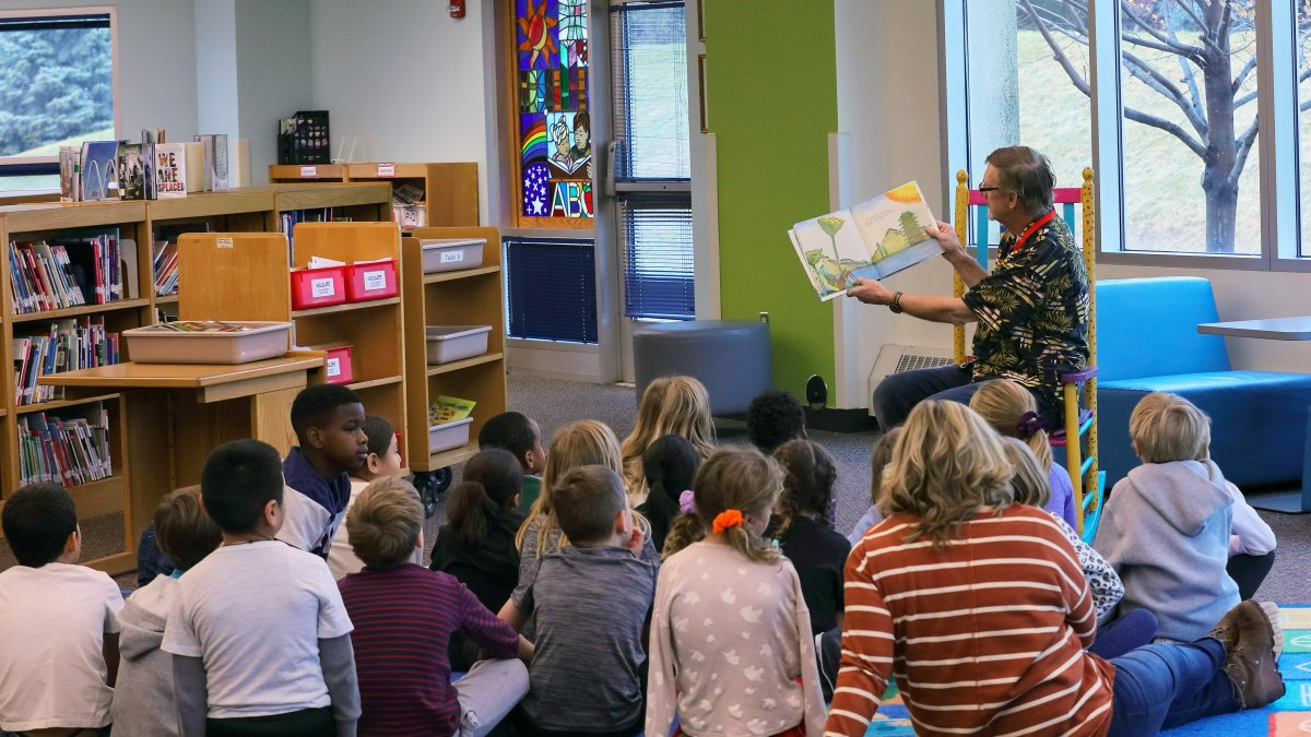 A staff member reads to a group of students in the media center
