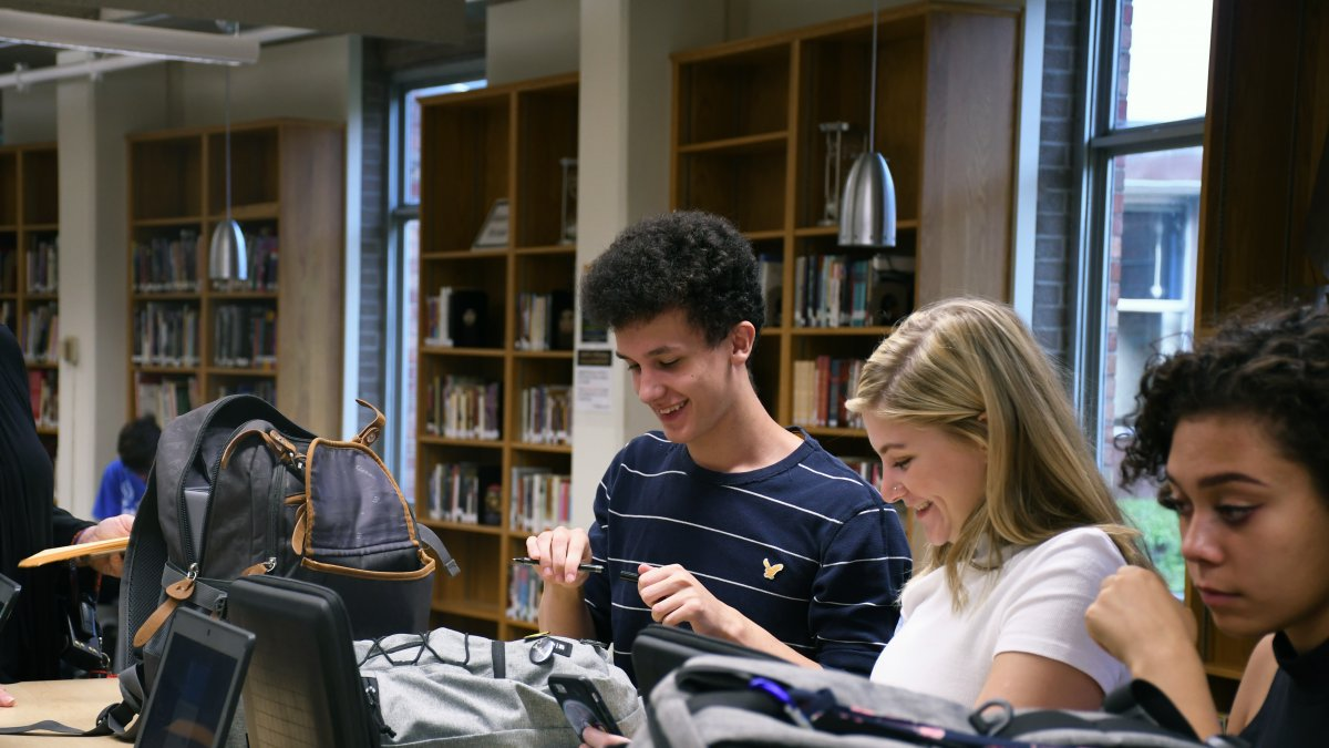 Students work on laptops in the media center