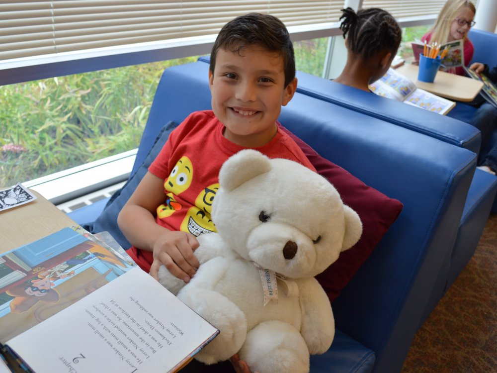 boy reading with teddy bear