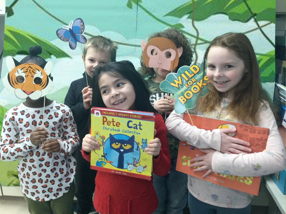 Kids holding books with a jungle background