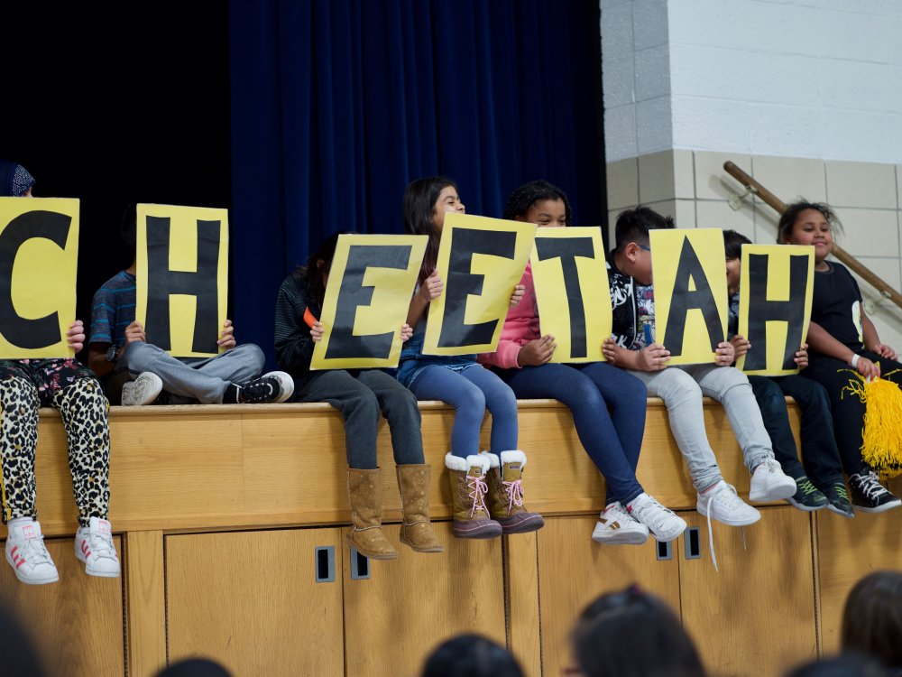 Kids holding a sign that spells out Cheetah