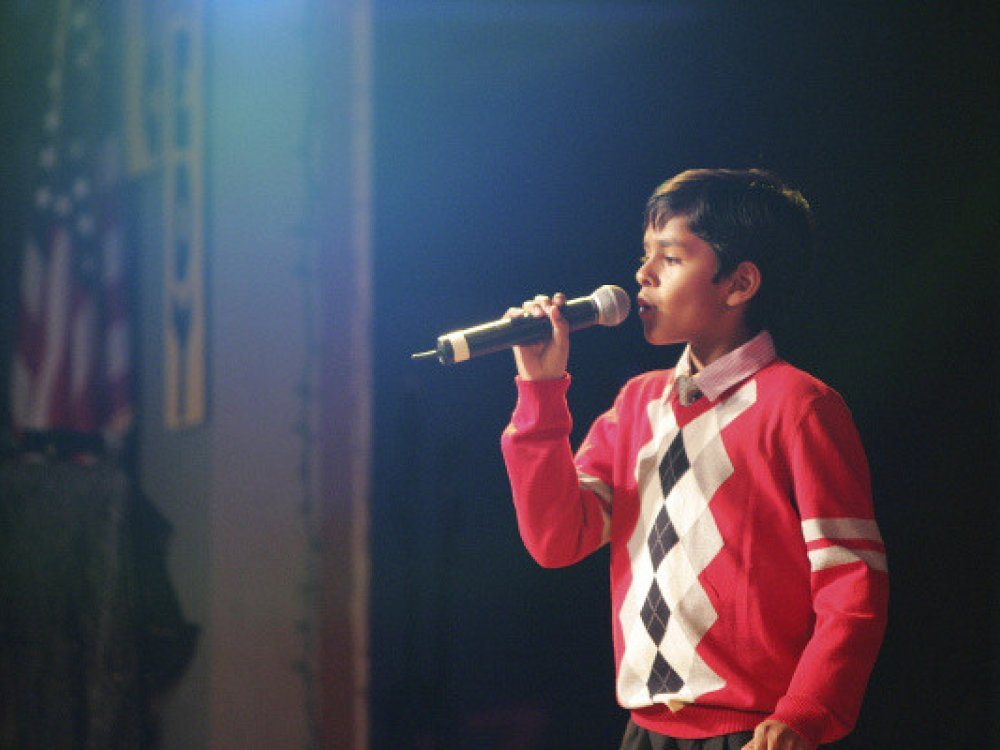 Boy in red sweater singing into a microphone