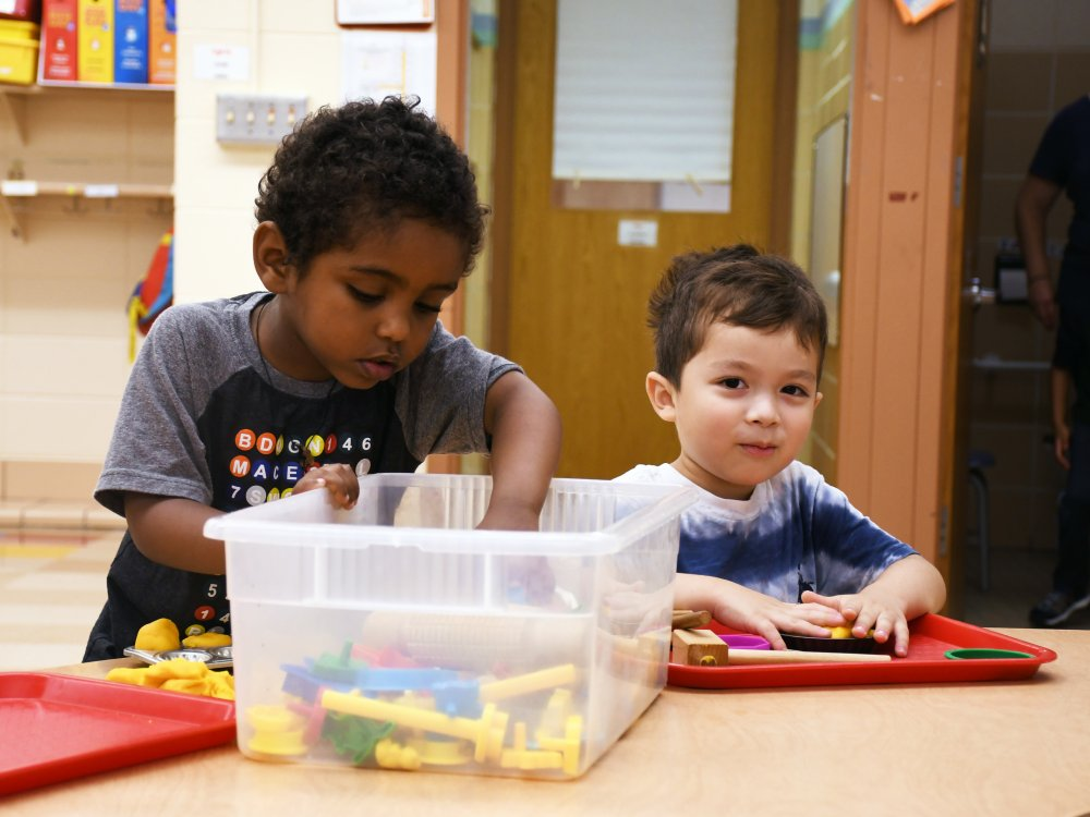 Two early learning students play with blocks at a table